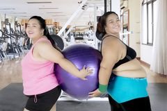Two overweight women holding a fitness ball. Two overweight women smiling at the camera while holding a fitness ball. Shot in the gym center Royalty Free Stock Image