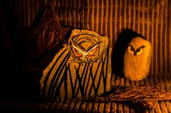Two owls sculptured from stone. Two sculptures of owls with interesting cartoon like features  sitting on straw as a mock nest or perch, slatted wooden Royalty Free Stock Photo