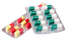 Two packages with red green yellow pills on white background Royalty Free Stock Image