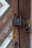 Two padlocks on old wooden door Royalty Free Stock Photos