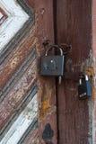 Two padlocks on old wooden door. Two metal lock on an old wooden door Royalty Free Stock Photos