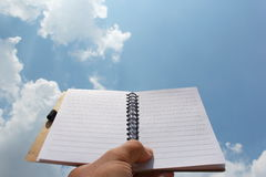 Two page notebook in hand on the background of sky Stock Photo