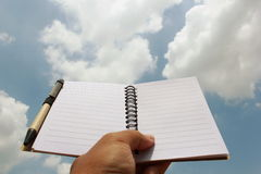 Two page notebook in hand on the background of sky Stock Images