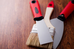 Two paint brush and spatula between them Stock Photos