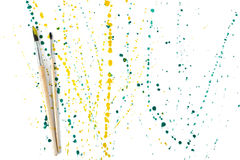 Two paint brushes with colorful gouache sprays and splashes on a white background. Art composition Royalty Free Stock Photography