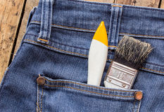 Two paint brushes in jeans pocket Stock Photos