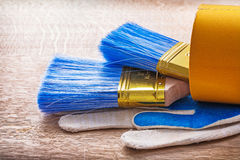 Two paint brushes in roll of duct tape and working Royalty Free Stock Photography
