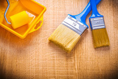 Two paint brushes roller and tray on woden board Royalty Free Stock Photo