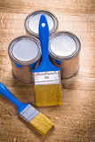 Two paint brushes and three cans on wooden board. Construction concept Royalty Free Stock Photos