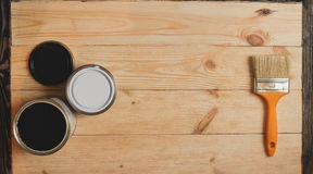 Two paint tins and brush on wooden background with copy space in center, top view Stock Photos