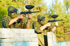 Two paintball players. Two paintball sport players in prootective uniform and mask aiming and shoting with gun outdoors Stock Photos