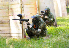 Two paintball players behind wooden fortifications Royalty Free Stock Photography