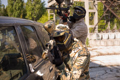Two paintball players hiding. Beside a car royalty free stock photos