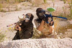 Two paintball players hunting outdoors. Over nature background stock image