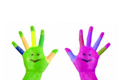 Two painted colorful hands with smiling faces. On the palms and fingers raised up. Isolated on white background Royalty Free Stock Photo