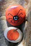 Two painted Halloween rocks of spider and pumpkin stock photo