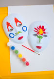 Two painted masks and paitnings on the table Stock Photos