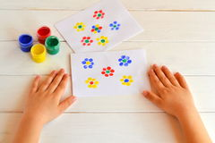 Two paintings of flowers painted children fingers. Jars with gouache. Children hands are on the table. Children early development. Development of fine motor royalty free stock photography