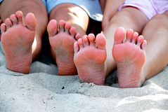 Two Pair of Bare Feet. Covered by beach sands royalty free stock photo