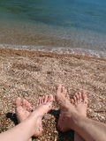 Two pair bare foot. On the sea coast Royalty Free Stock Photo