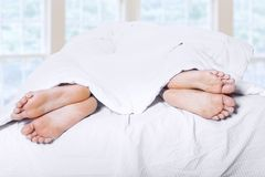 Two pair of feet on bed 1 Stock Images