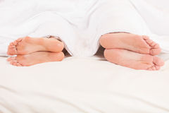 Two pair of feet far from each other in bed. Closeup of four feet in bed lying Royalty Free Stock Photo