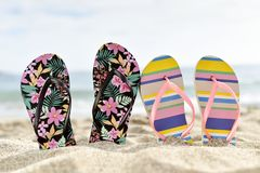 Two pair of flip-flops on the beach. Closeup of two different pairs of colorful flip-flops, one of them flower-patterned and the other striped, stuck on the sand royalty free stock photography