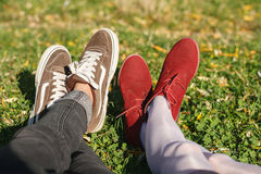 Two pair of legs on grass. Two pair of male and female legs in shoes lying on green grass Stock Images