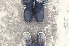 Two pair of legs wearing winter shoes stand opposite each other on snowy road royalty free stock image