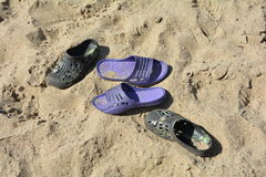 Two pair of shoes on the sandy beach Stock Images