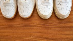 Two Pair Of White Sneaker Shoes Top View. On A Wooden Surface Stock Images