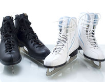 Two pairs of black and white figure skates. On white background Stock Image