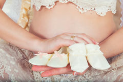 Two pairs of children`s pinets on the background of the belly of a pregnant mother. Waiting for twins. Two pairs of children`s pinets on the background of the Royalty Free Stock Photography