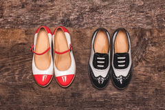 Two pairs of children`s shoes top view. On a wooden surface Stock Photos
