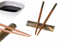 Two pairs of chopsticks and soy sauce. Two pairs of wooden chopsticks and soy sauce. Sticks are decorated with temple theme ornamentation. Isolated on white Stock Photo