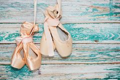 Two pairs of ballet shoes. Two pairs of classic ballet shoes - new and used - hang on their ribbons on rough painted wooden background. After ballet dancing show Royalty Free Stock Photography