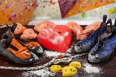 Two pairs of climbing shoes lie next to the climbing hook in the form of a heart. In the foreground, the rope passes through the c stock images