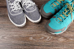 Two pairs of colorful sneakers laid on the wooden floor background Stock Photos