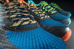 Two pairs of colourful exercise trainers / running shoes. Inside a gym royalty free stock images