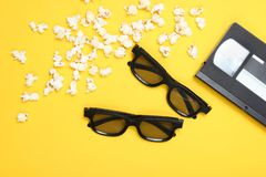 Two pairs 3D glasses, popcorn, video cassette. On yellow background. Retro style. Top view, flat lay royalty free stock photo