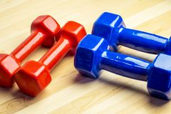 Two pairs of dumbbells for a sporting class at home for all family members. A wooden background Stock Photography
