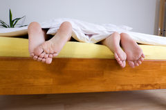 Two pairs of feet in bed Royalty Free Stock Photos