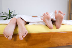 Two pairs of feet in bed Royalty Free Stock Image