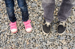 Two pairs of feet in sneakers, adults and children, are on the pebble. Two pairs of feet in sneakers, adults and children, are on pebble Royalty Free Stock Images