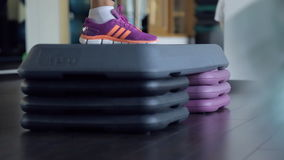 Two pairs of feet in sneakers carry out exercise on a step. Step on three levels and is painted in blue and purple colors. Sport inventory springs at each step stock footage