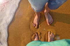 Two pairs of feet stand on the sand and wait for the wave to come. wave on sandy beach of Kalutara, Sri Lanka. Two pairs of feet stand on the sand and wait for stock images