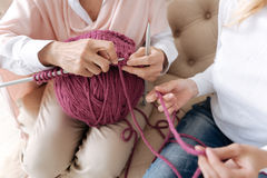 Two pairs of female hands doing knitwork. Pleasant pastime. The close up of two pair of female hands with one of them holding a thread and the other knitting and Stock Photography