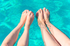 Two pairs of female legs. In the pool Stock Images