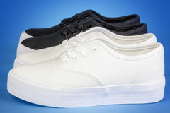 Two pairs Flatform Plimsolls in white and black on blue Stock Photos