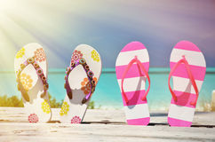 Two pairs of flip-flops. Against Atlantic. Exuma, Bahamas Royalty Free Stock Photos